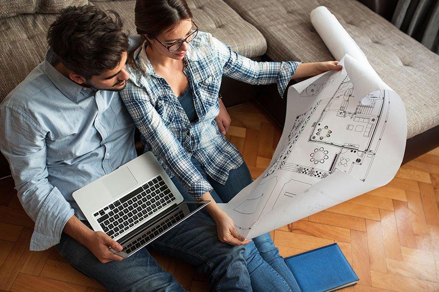 una coppia con un progetto di una casa in mano e un computer portatile