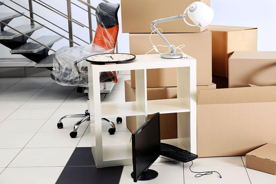 un mobiletto bianco, una lampada, una tv e degli scatoloni