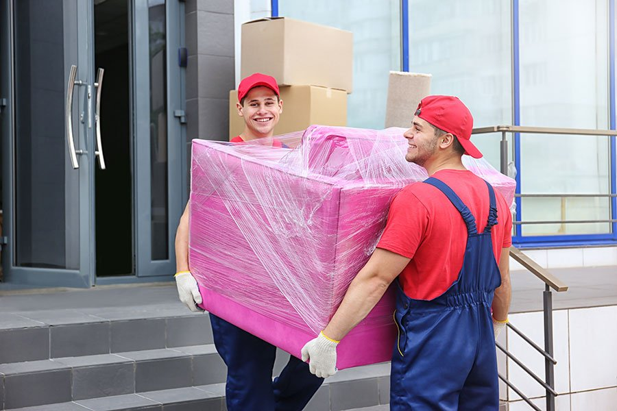due traslocatori che sollevano una poltrona rosa