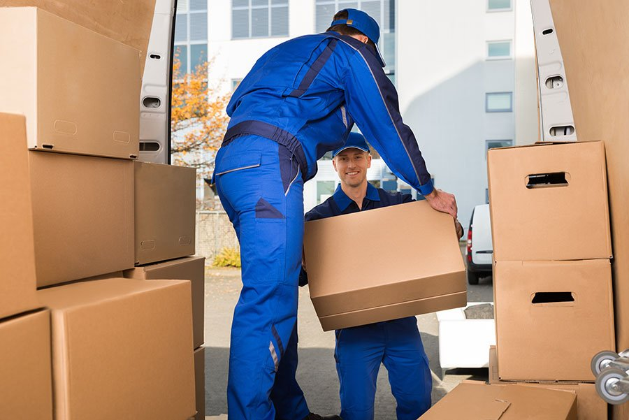 due traslocatori che caricano sul camion degli scatoloni