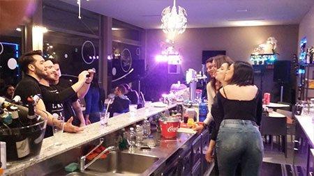 dei ragazzi che scattano delle foto a delle ragazze dietro il bancone del bar