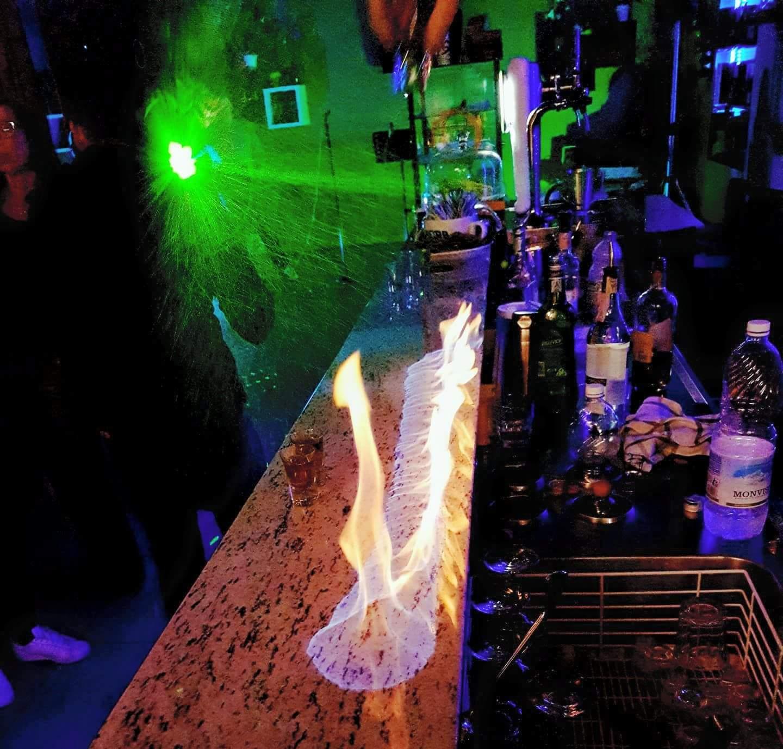 il bancone del bar con delle luci verde e delle bottiglie di alcolic