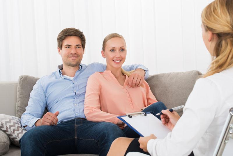 una coppia sorridente seduta davanti a una psicologa