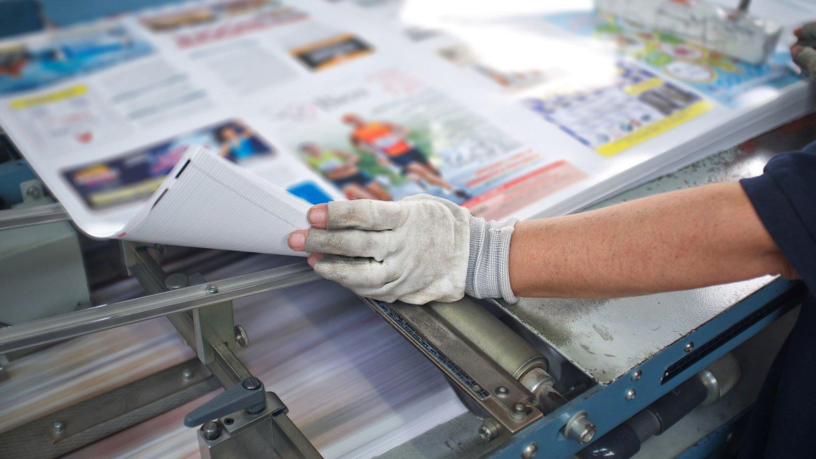 una mano con un guanto e una brochure appena stampata