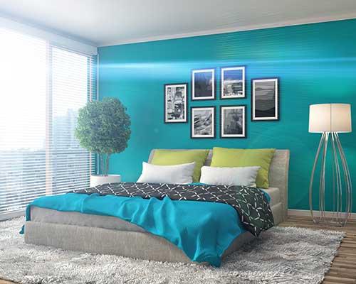 Camera da letto verde e blu, tappeto grigio, quadri e un piccolo albero