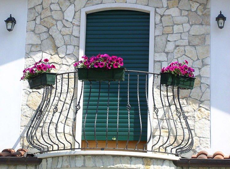un balcone in ferro battuto con tre vasi di fiori appesi