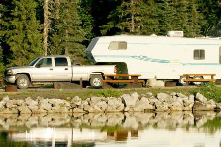 truck towing a travel trailer to a campsite