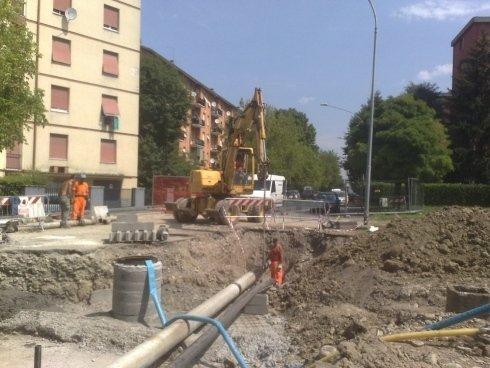 degli uomini al lavoro con dei mezzi in uno scavo
