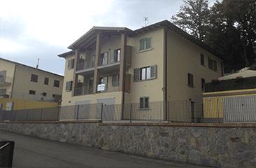 un condominio giallo con persiane verdi alle finestre