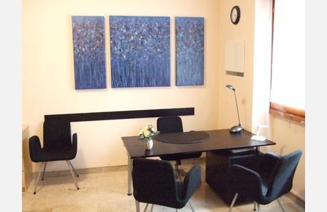 studio Otorinolaringoiatra con tavolo, sedie e parete decorate