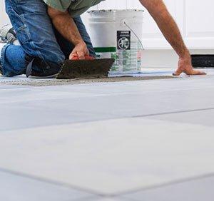 Man laying DIY tiles