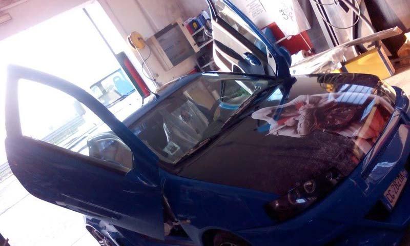 una macchina azzurra vista di lato