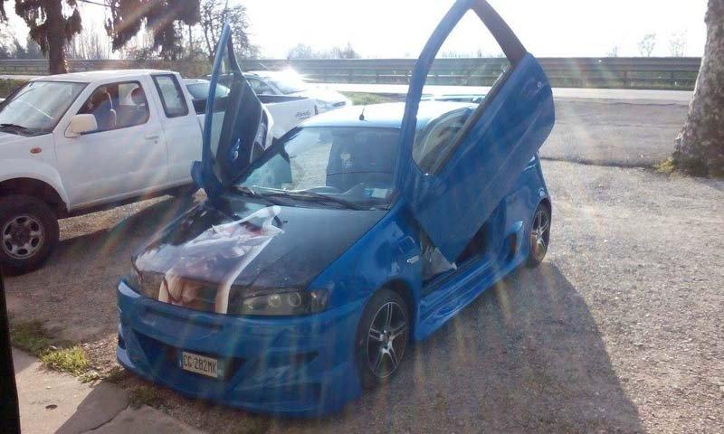 auto blu con portiere aperte all'aperto