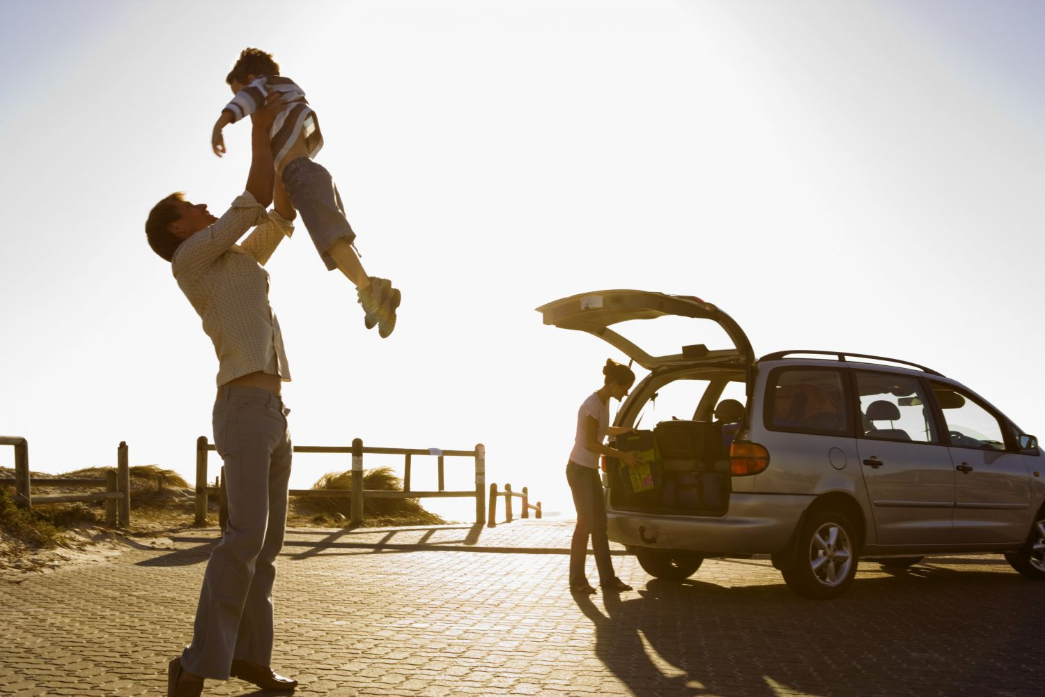 Man holding child next to a trade car