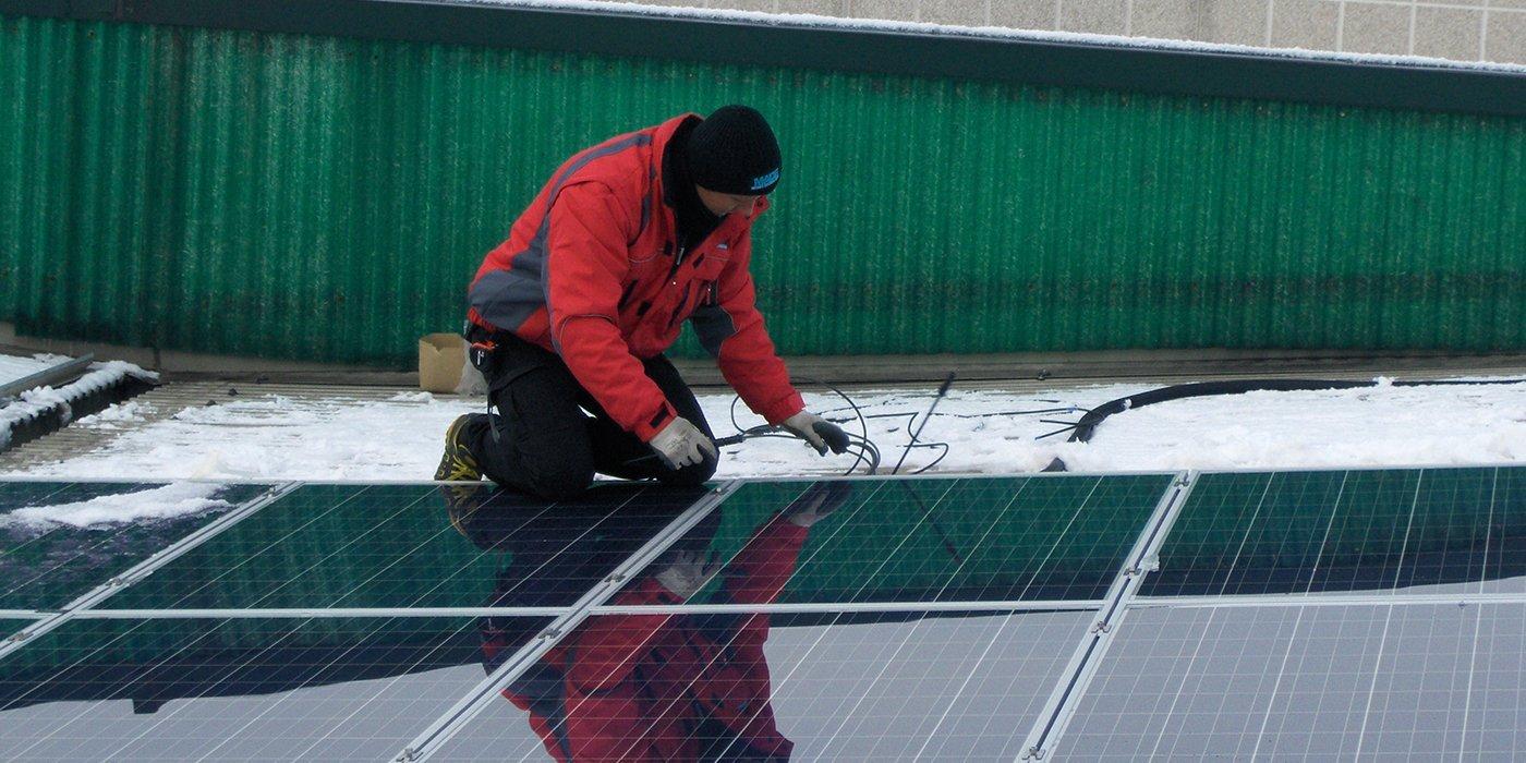un operaio con un giubbotto rosso e un cappellino di lana nero chinato a terra mentre installa dei pannelli solari