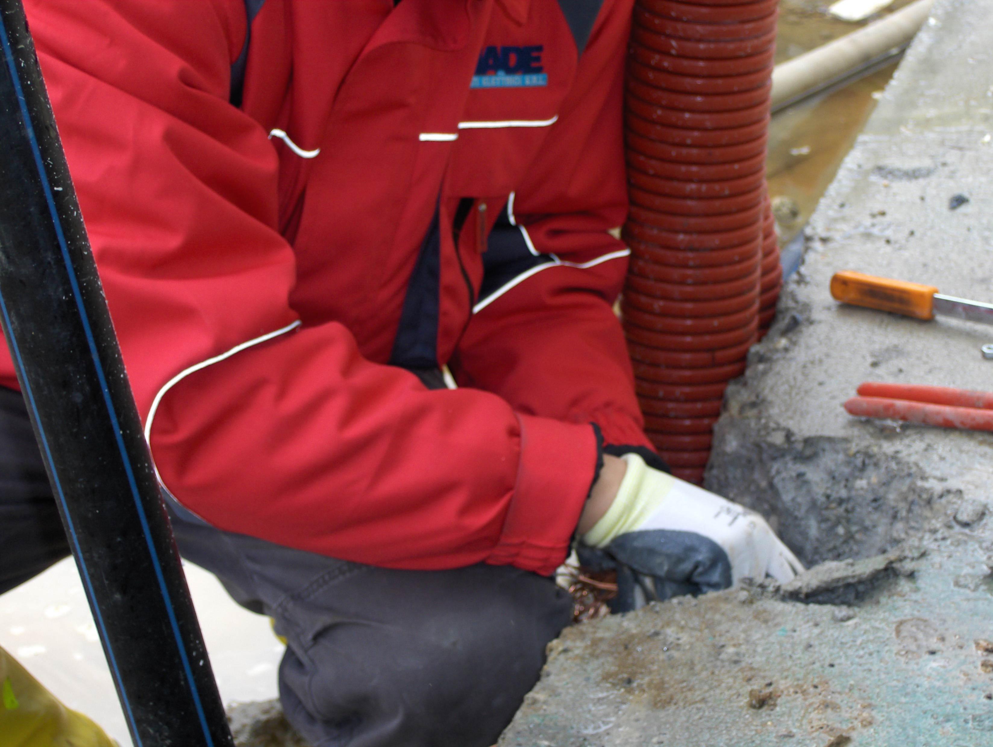 un uomo con una giacca rossa chinato a terra mentre sta effettuando una riparazione in un terreno scavato