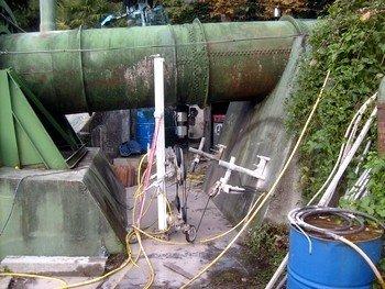 un grosso tubo verde di un condotto e sotto dei cavi