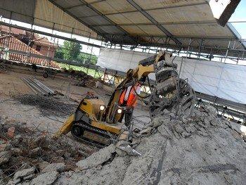 un mezzo da lavoro con una morsa durante un lavoro di demolizione