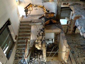 un mezzo da lavoro durante una demolizione all'interno di uno stabile