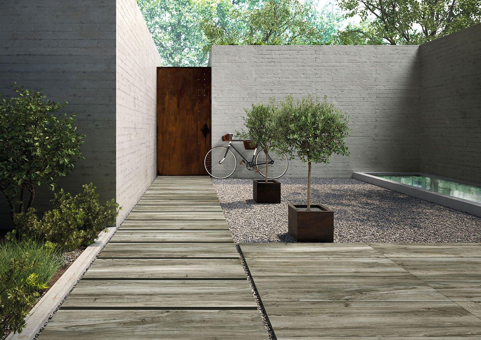 una passerella in legno in un cortile con della ghiaia, dei vasi con delle piante e una bici