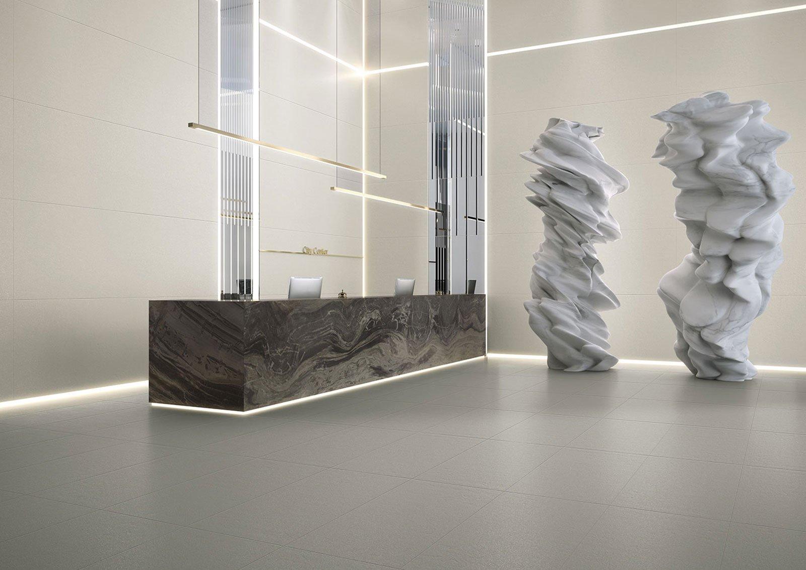 un bancone di una reception marrone e due statue futuristiche grigie