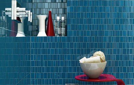 un bagno con muri neri wc,bidet e  un lavabo e sotto un mobiletto viola
