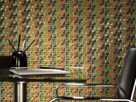 una scrivania di vetro,una poltrona nera e una parete dipinta di diversi colori