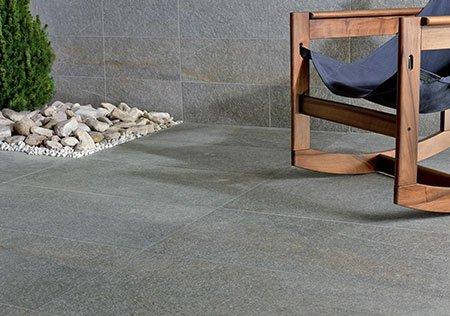 delle piastrelle grigie, dei sassi con una pianta al centro e una sedia in nylon blu e legno