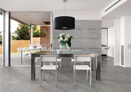 una sala da pranzo con un tavolo al centro con delle sedie e una lampada a sospensione nera
