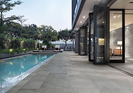 delle piastrelle grigie a bordo piscina e sulla destra vista delle finestre aperte di una casa