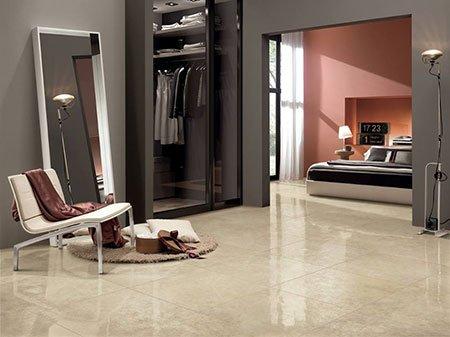 una stanza con una sedia beige sulla sinistra, un armadio con dei vestiti e vista di una camera da letto