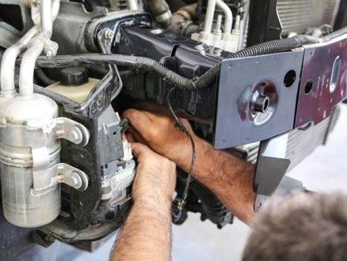 meccanico mentre sistema il motore di un auto