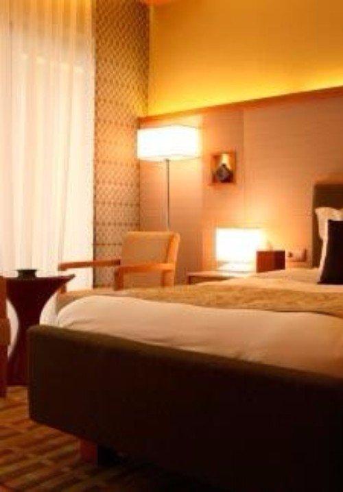 una camera con un letto, due sedie e una lampada da terra