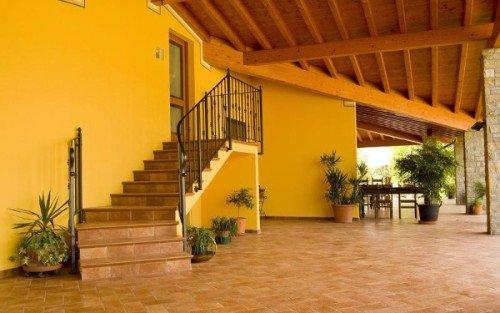 una veranda con un tetto in legno e dei vasi di fiori