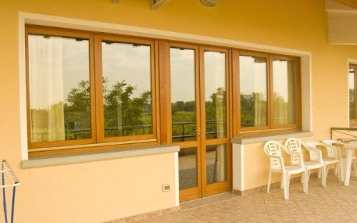 delle finestre di una stanza e delle sedie in plastica in una terrazza
