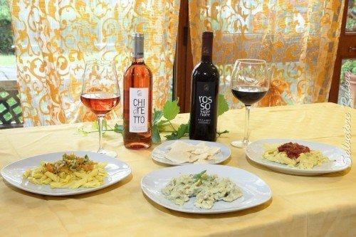 un tavolo con dei piatti di pasta e due bottiglie di vino