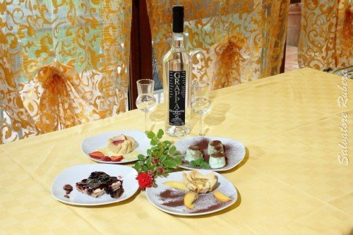 un tavolo con piatti di dolci e una bottiglia di grappa