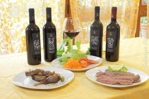 due piatti a base di carne e delle bottiglie di vino rosso
