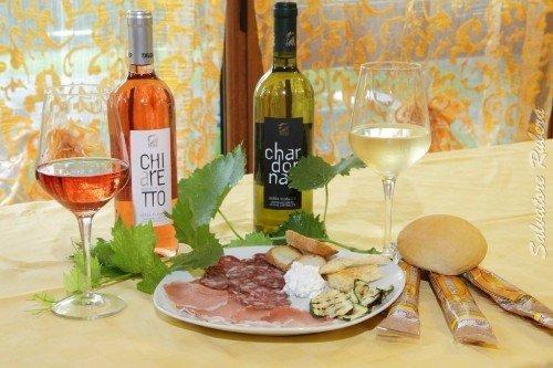 un piatto di salumi e due bottiglie di vino bianco e rose'
