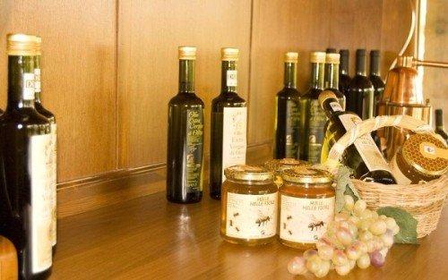 una mensola con delle bottiglie di olio d' oliva e dei barattoli di miele