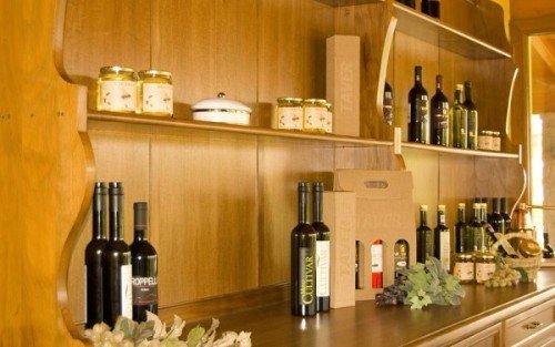 un mobile con delle bottiglie di vino, olio d' oliva e dei barattoli di miele