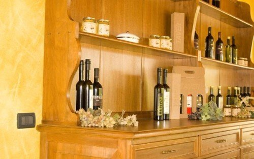 un mobile con delle bottiglie di vino, olio d' oliva e dei barattoli di marmellata