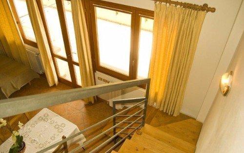 una sala con un divano, delle finestre e un tavolo con le sedie