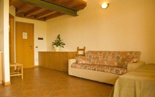 una sala con un tavolo, una Tv e vista delle scale Aziende-agricole-manerba-del-garda