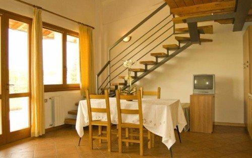 una cucina in legno e vicino un tavolo con le sedie