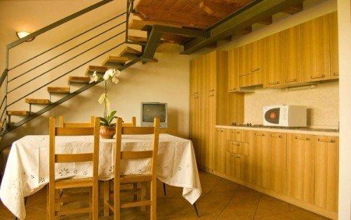 un tavolo con delle sedie, una cucina con mobili in legno e una scala