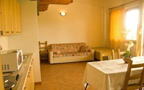 un monolocale con una cucina, un divano e un letto singolo