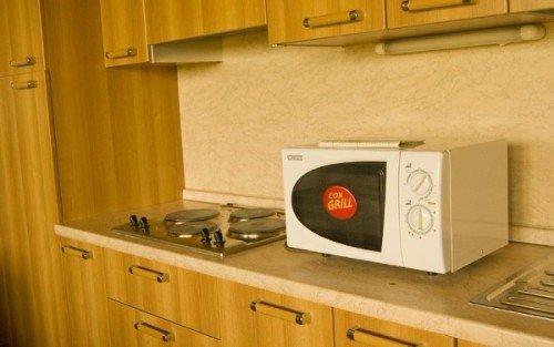 una cucina con fornelli a induzione e un microonde accanto