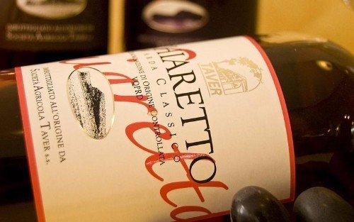 una bottiglia di vino e accanto dell'uva