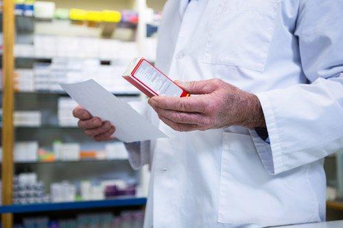 farmacista consulta una ricetta e legge le indicazioni scritte sulla confezione di un farmaco